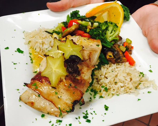 Grilled Mahi Mahi with starfruit and sautéed veggies over a bed of rice at Little Harry's.