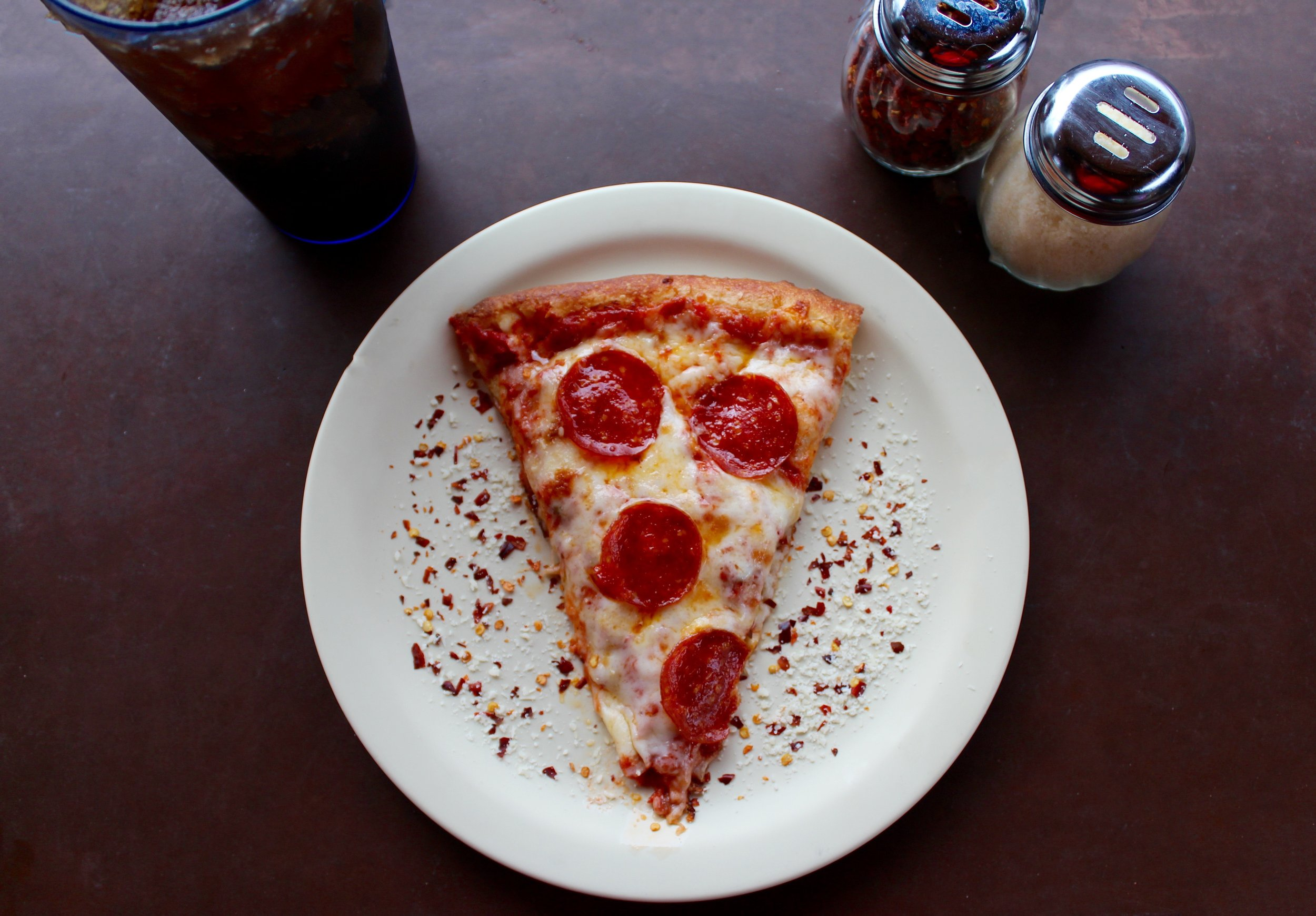 A slice of pepperoni pizza with a soda and parmesan shakers.