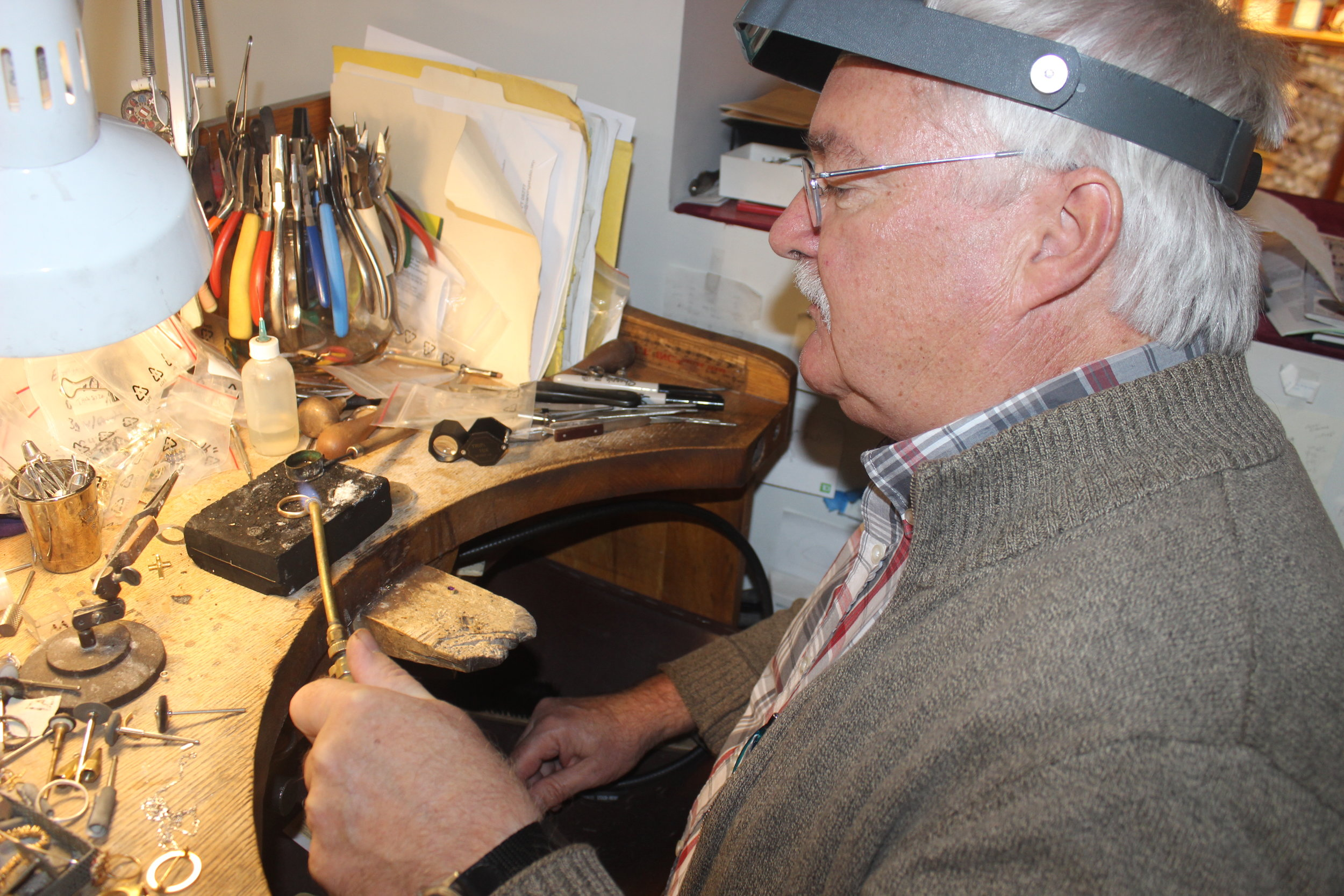 Tim Schneller crafts a ring at his workbench in Timco Jewelers at 59 Center Street.