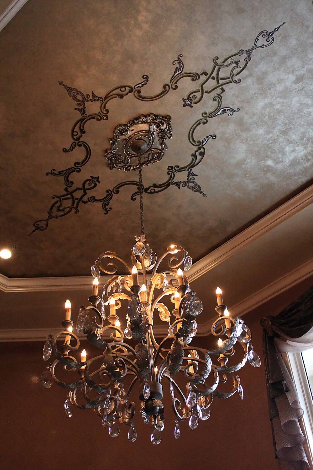 This ceiling was plastered with multiple metallic plasters accompanied with a custom embossed design with a textured plaster & highlighted with gold and silver metallics.