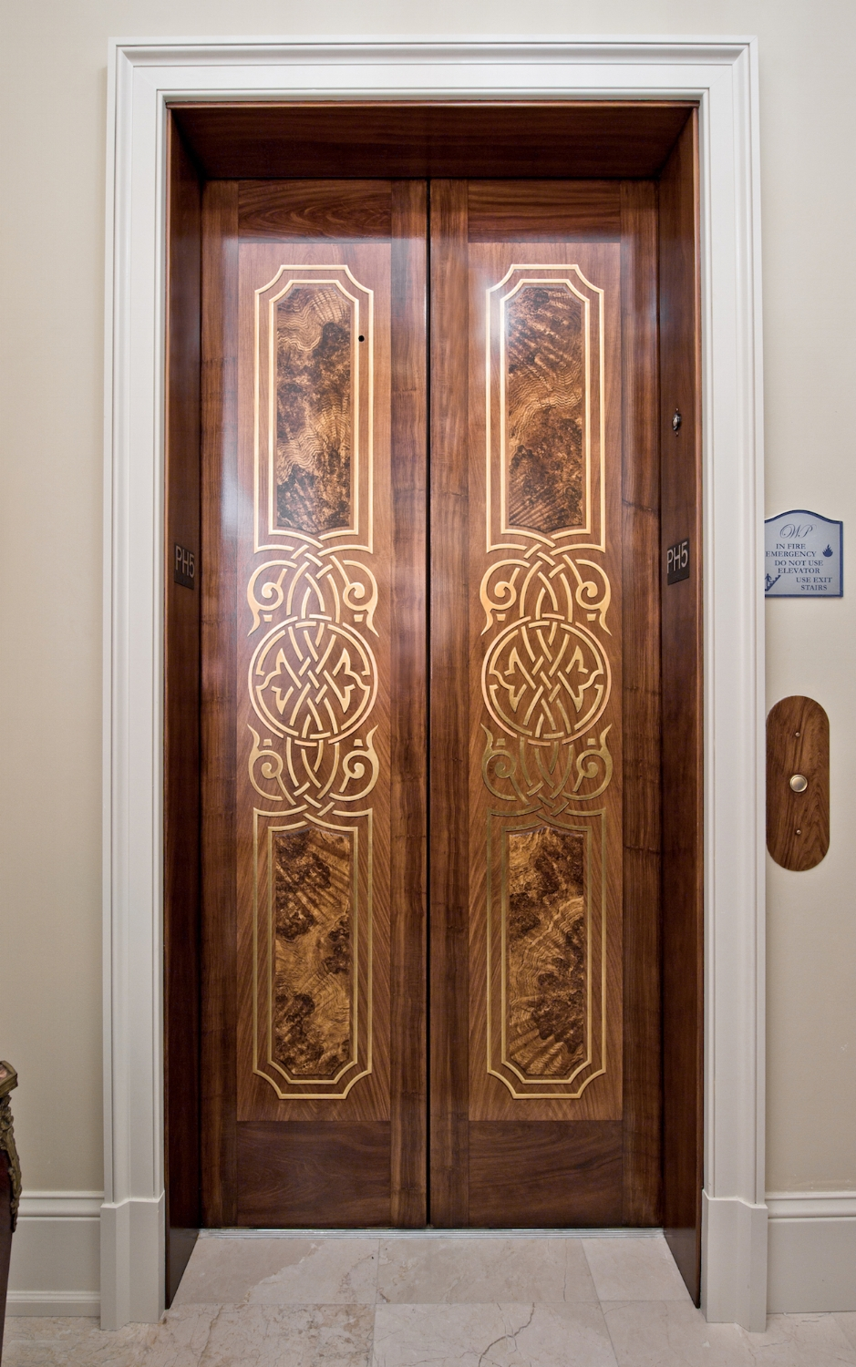 These stainless steel elevator doors were painted using a woodgraining technique. The custom design on the doors were gilded using Japanese Colored Silver Leaf.