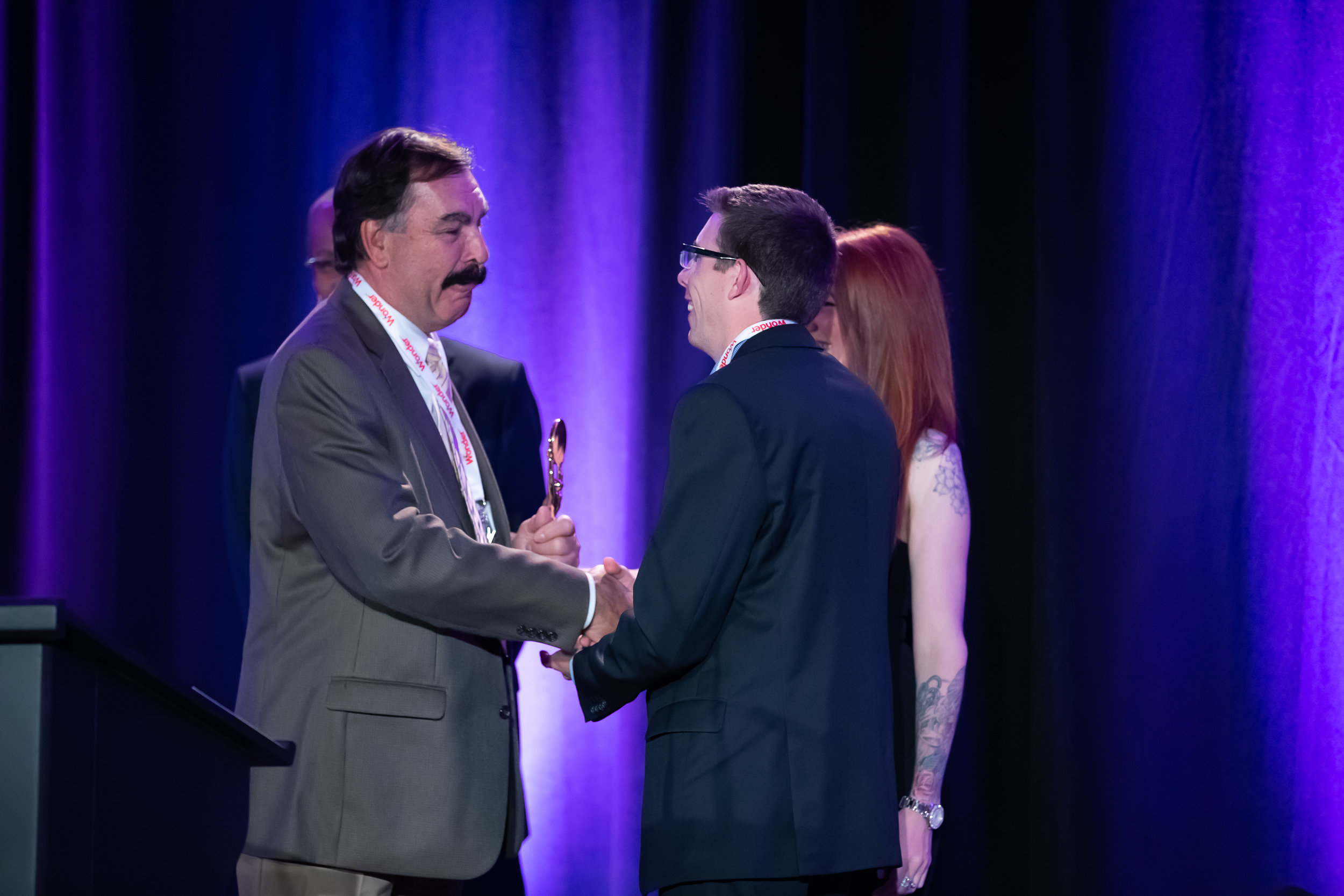 Bob Brema (William M. Dunne & Associates) shakes hands with DCI Treasurer Nigel Oliver of Vince's Market and Star Awards Presenter Melissa Lynne-Schaffer