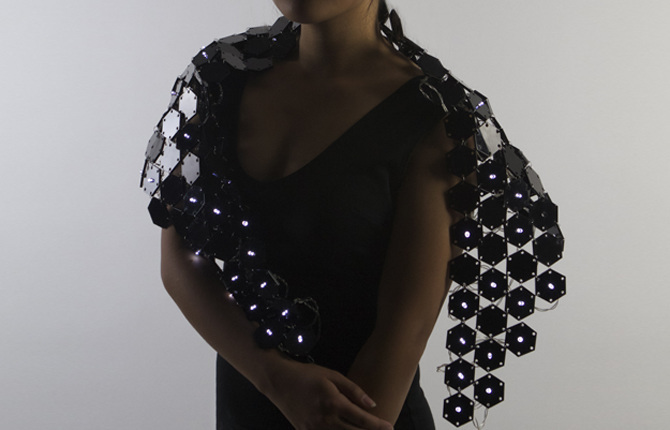 Shawl    With laser-cut tessellated black acrylic sheets designed in Illustrator, I created a futuristic shawl that incorporates LED lights and laser-cutting technology as a new medium for wearable items.