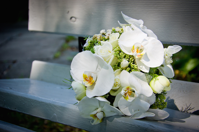 Wedding bouquet of white orchids lies on a bench in the garden.jpg