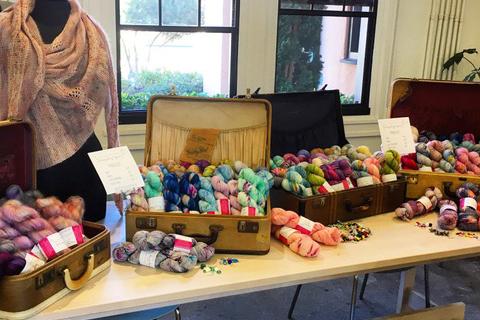Many skeins of yarn displayed in vintage suitcases.