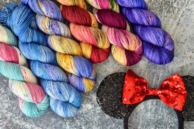 Variegated and tonal skeins next to a Minnie Mouse headband.