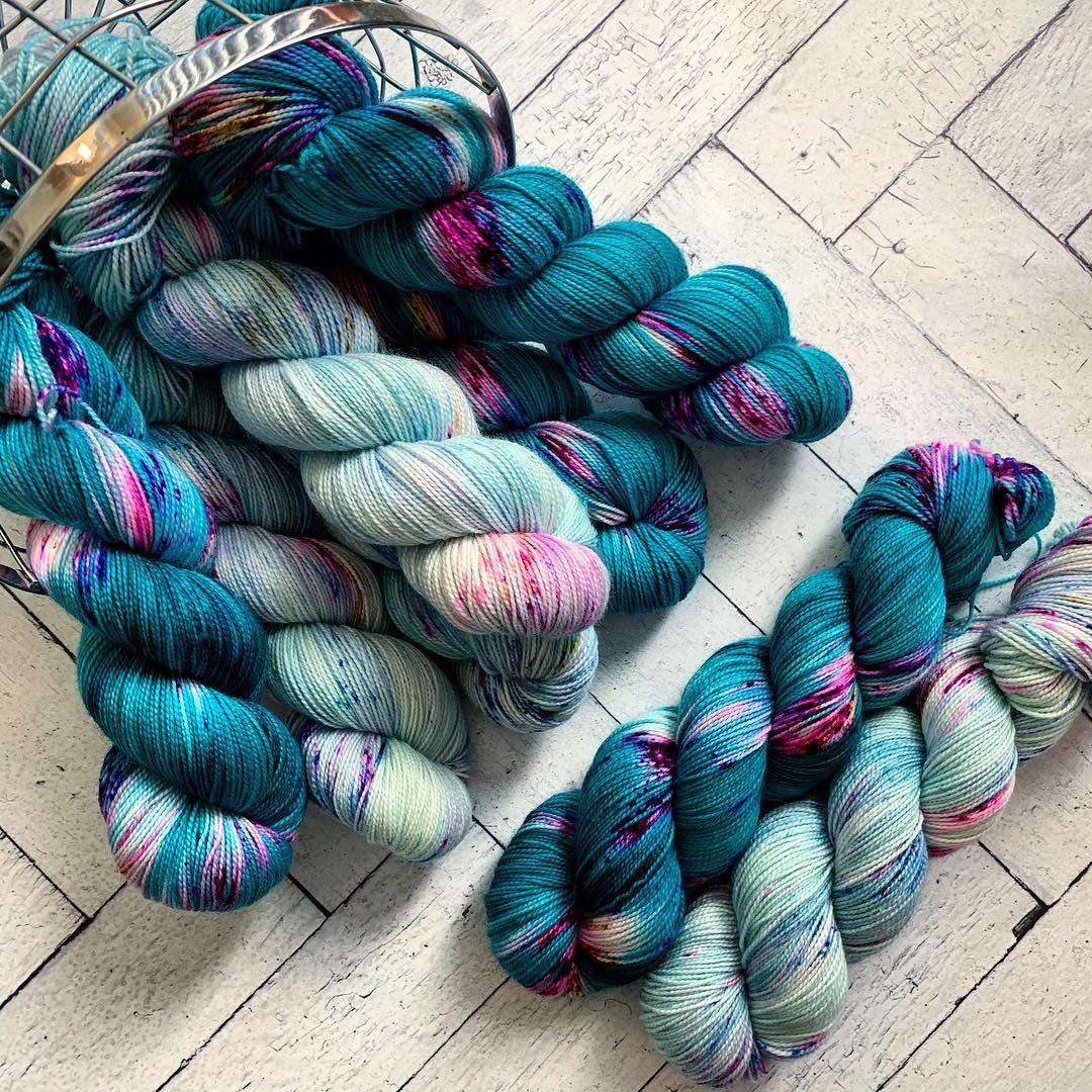 Multiple skeins of blue speckled yarn in a basket.