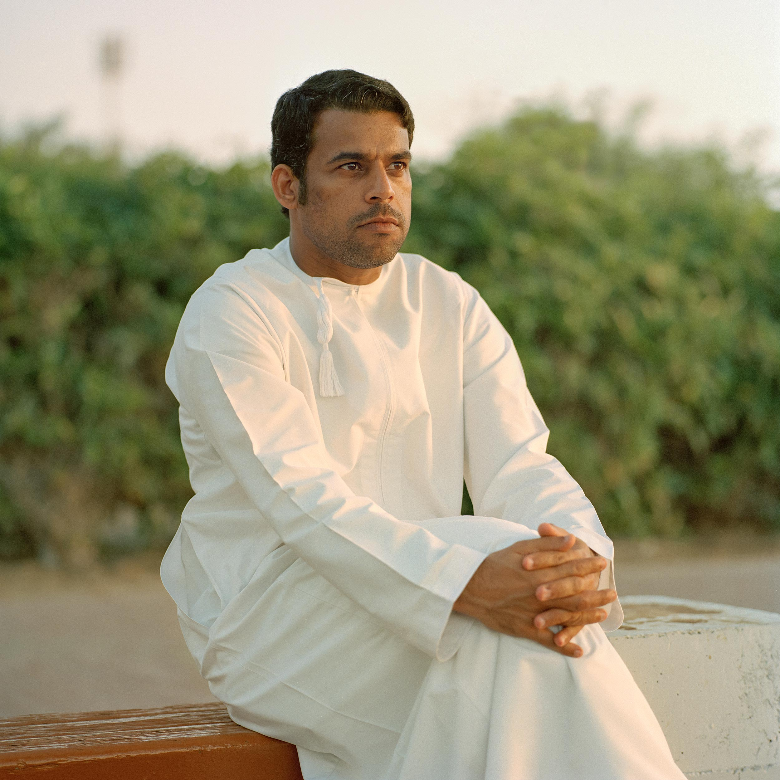 photograph of man sitting on bench wearing dishdasha from series XO