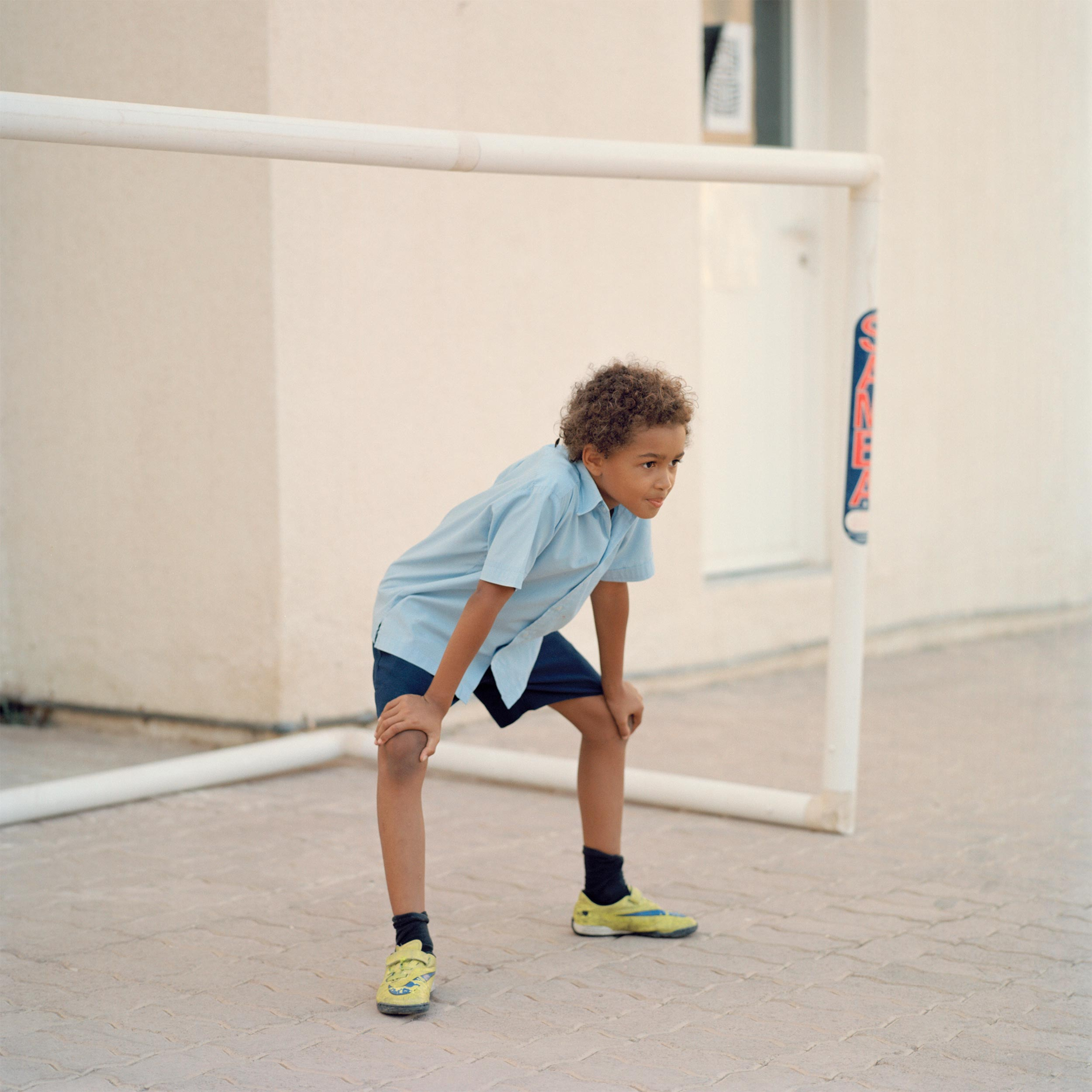 photograph of boy playing football from series XO