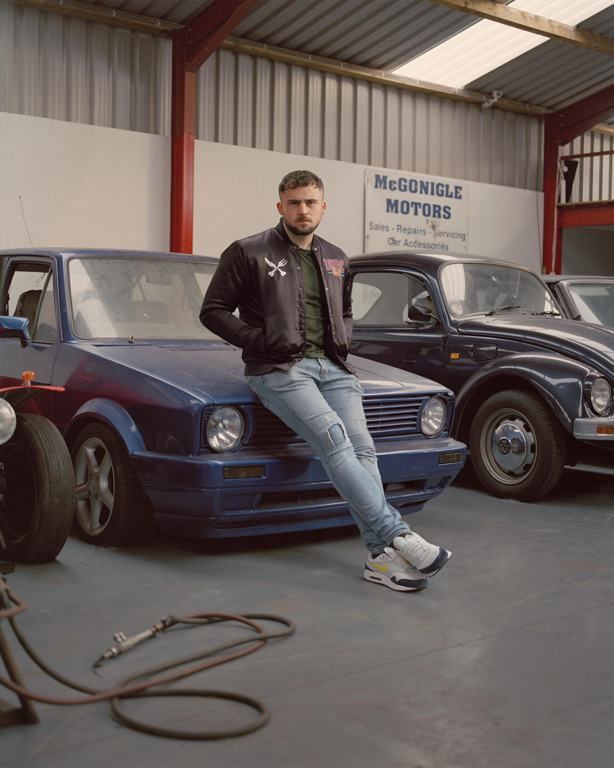 photograph of man leaning on car from series 99 Peace Walls