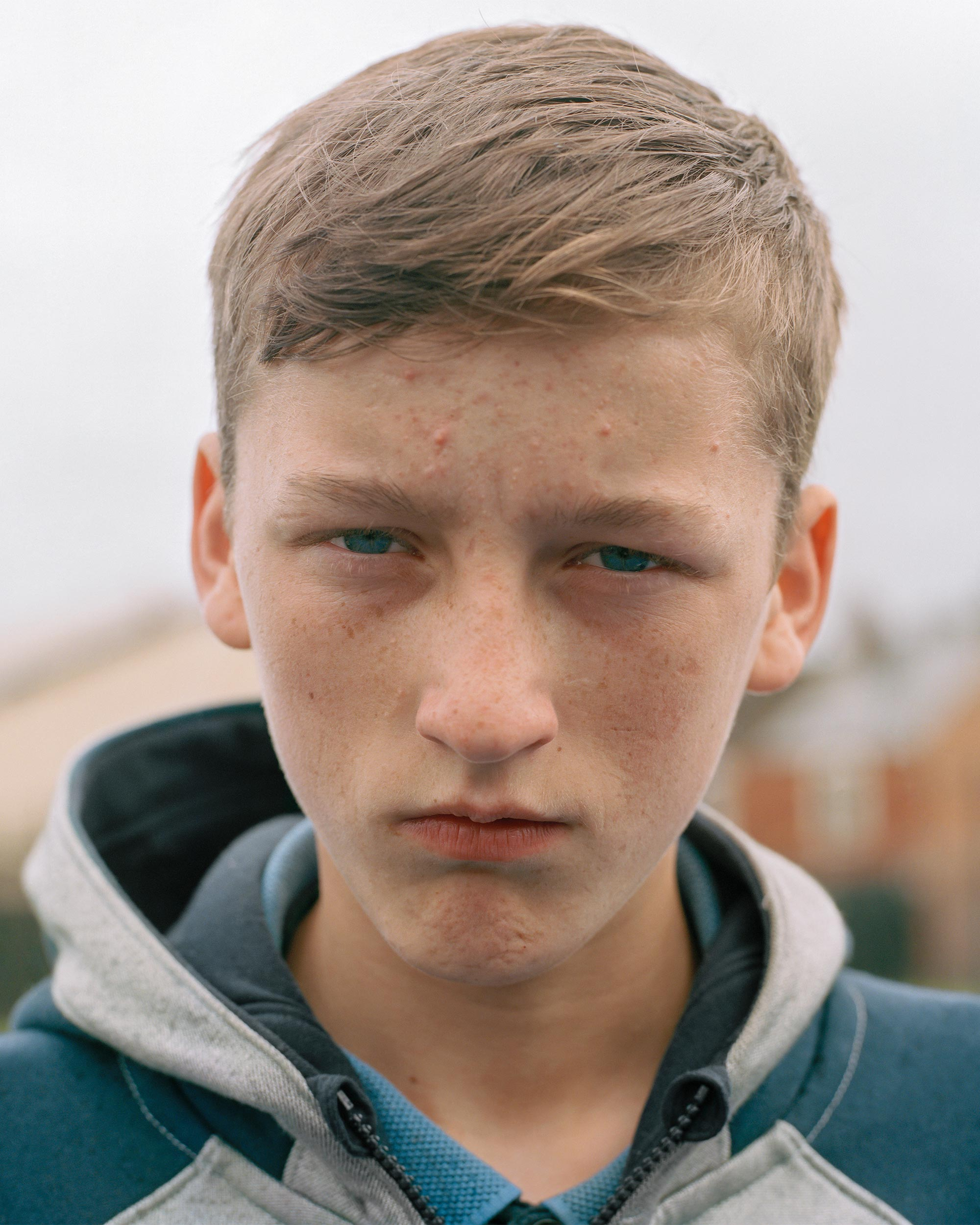 photograph of boy wearing hoodie outside