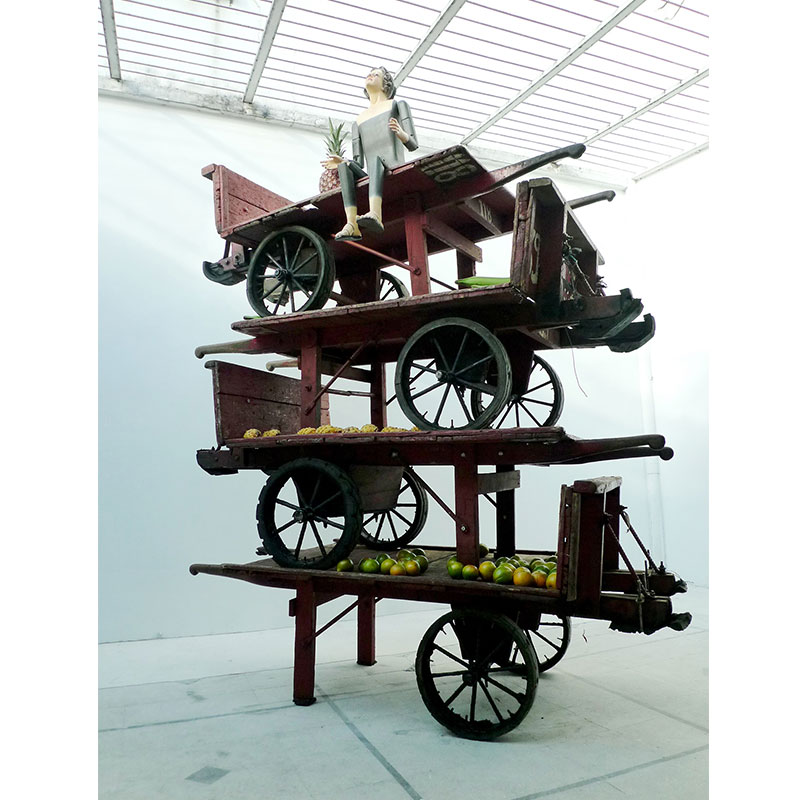 """The Virgin Mary of Medellin , 2011 wooden carts, painted wood mannequin, and fruit 103.5 x 83.5 x 36""""  Inquire >"""