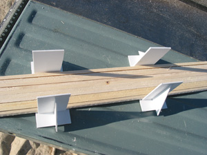 The next step is to bundle the ties for cross-cutting. A pair of home-made styrene cradles help establish a flat base for the tie bundle. Tie strips that are shorter due to knots are collected and made into shorter bundles.
