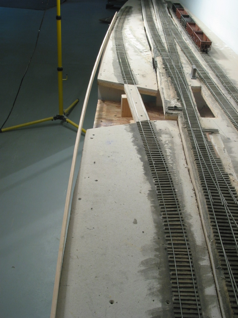 To create a smooth flowing edge for future fascia, a wood spline was initially set atop the plywood/micore base and a pencil line drawn. A saber saw completed job. A future pile trestle will carry a siding over the creek and be the main focus of this scene.