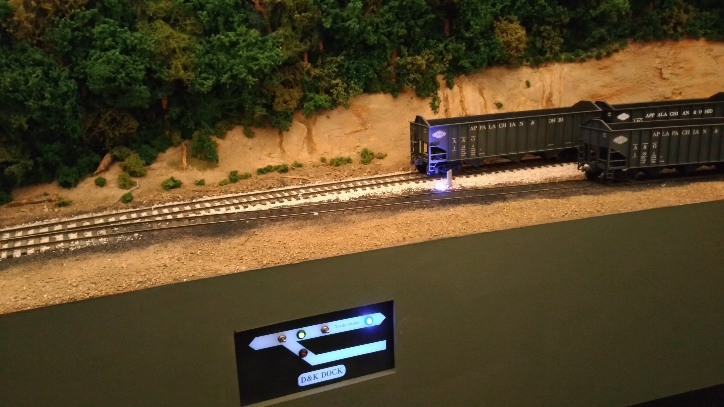 "Because the main is descending a grade, the small panel includes a ""Grade Brake"" to hold cars while switching the dock is performed. The LED's are blue: One on the panel next to actuating toggle, and one near the track. With the ballast surround, it is invisible unless lit.  A side-mounted Tortoise raises and lowers a wire between the rails to engage a wheel axle at the post indicator.   Blue LED? Blue Flag- ""Don't move this car."""