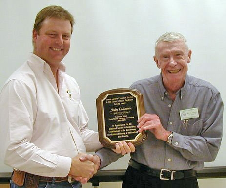 Left, AgriLife Extension Agent Roy Walston presents award to Hill Country Master Gardener co-founder John Coleman