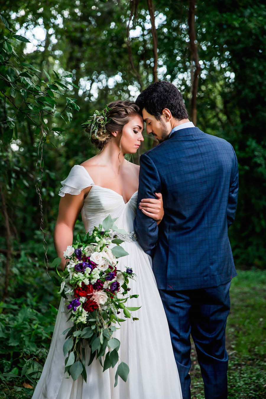 Bride wearing Amsale wedding dress from Blush Bridal Sarasota and Groom Portrait with Deep Red Burgundy Wedding Bouquet with Greenery | Southern Inspired Outdoor Wedding Reception Decor Styled Shoot