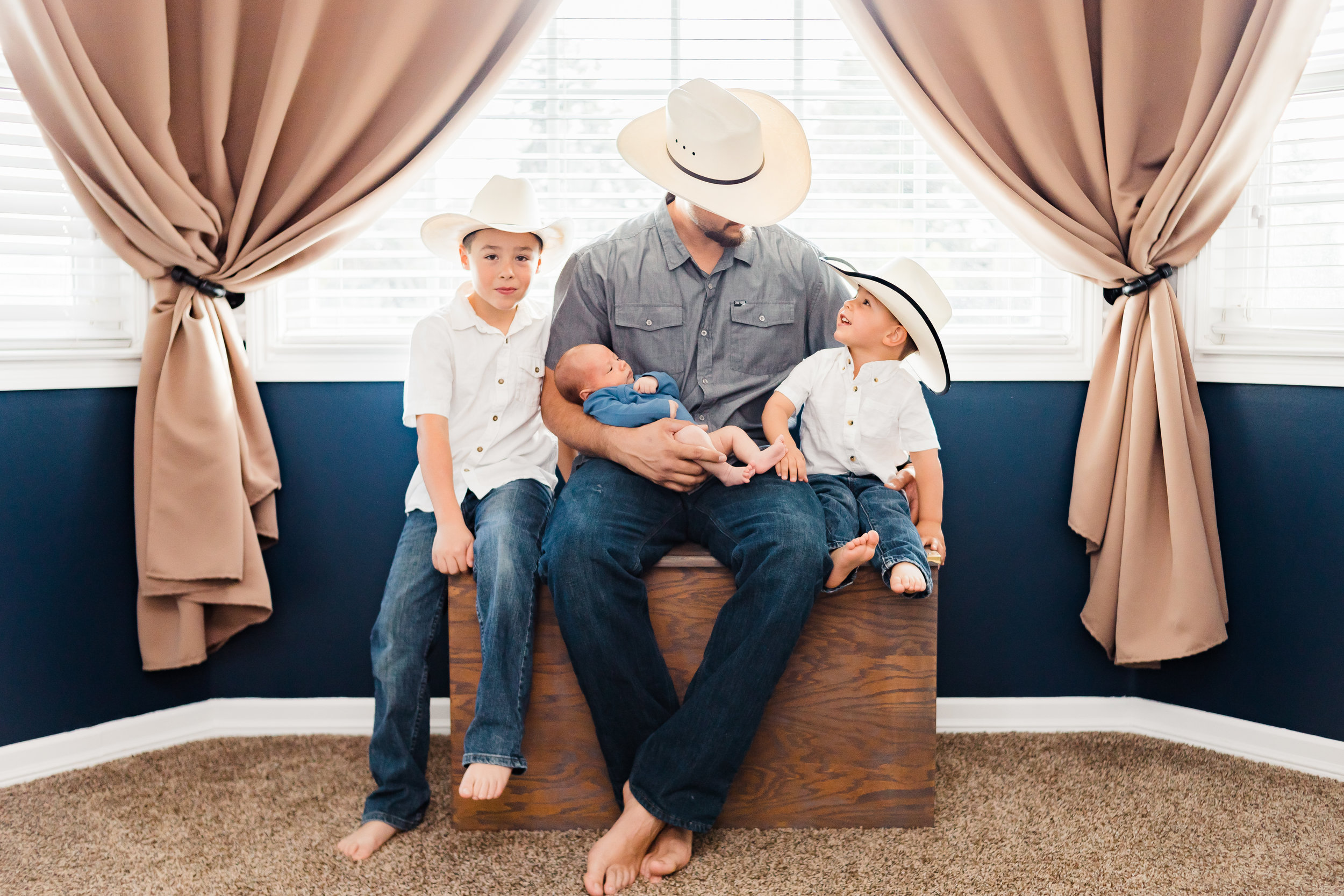 newborn lifestyle dad holding baby with brothers wearing cowboy hats