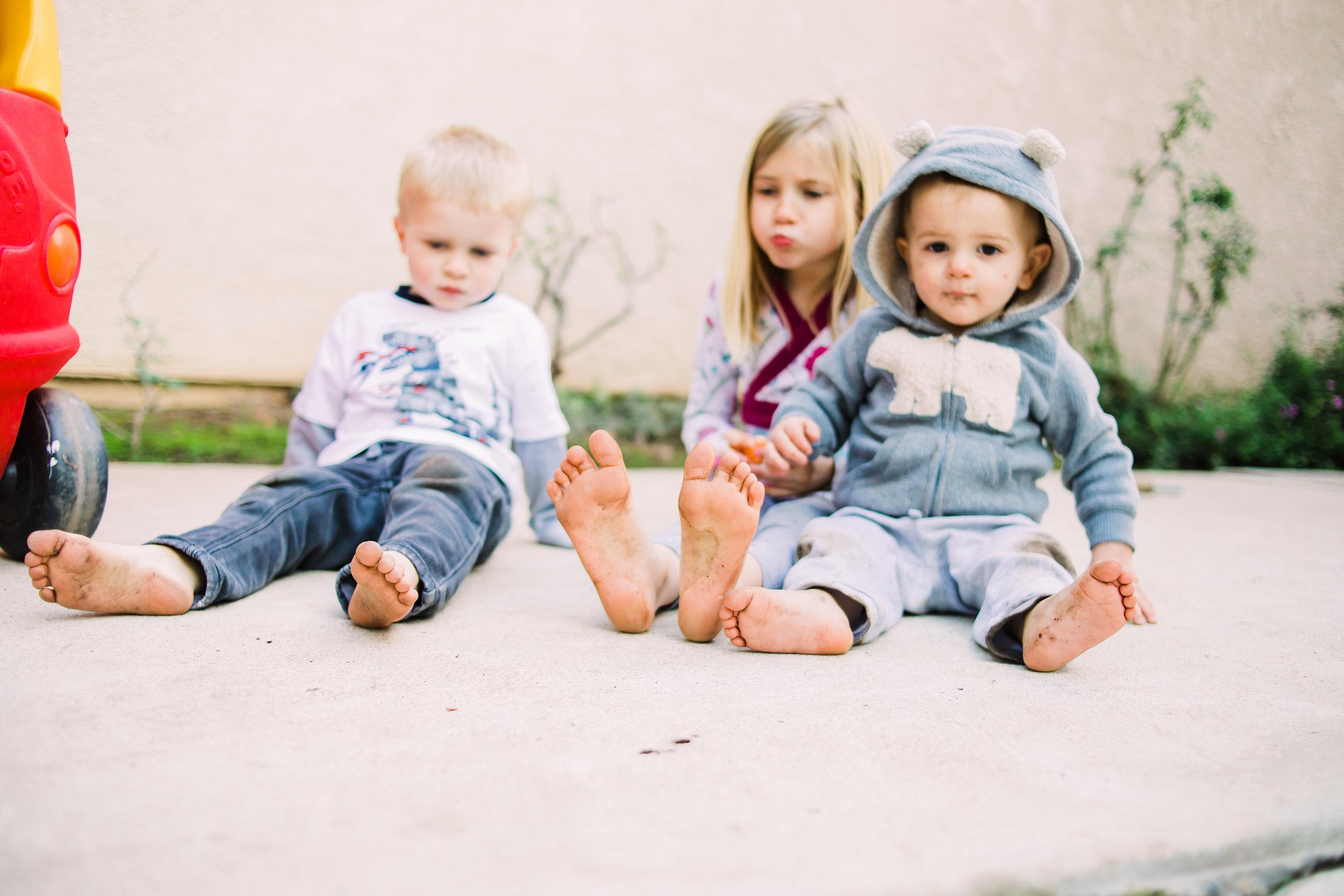 three kids sitting on a patio