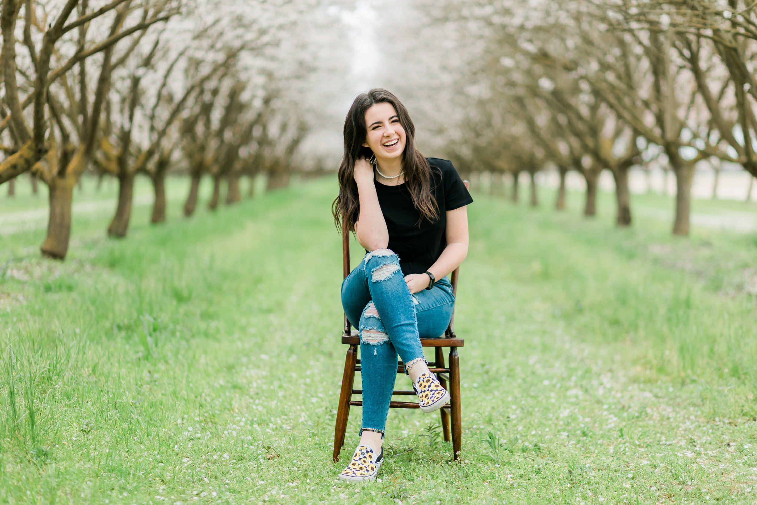 senior girl sitting on wooden chair laughing