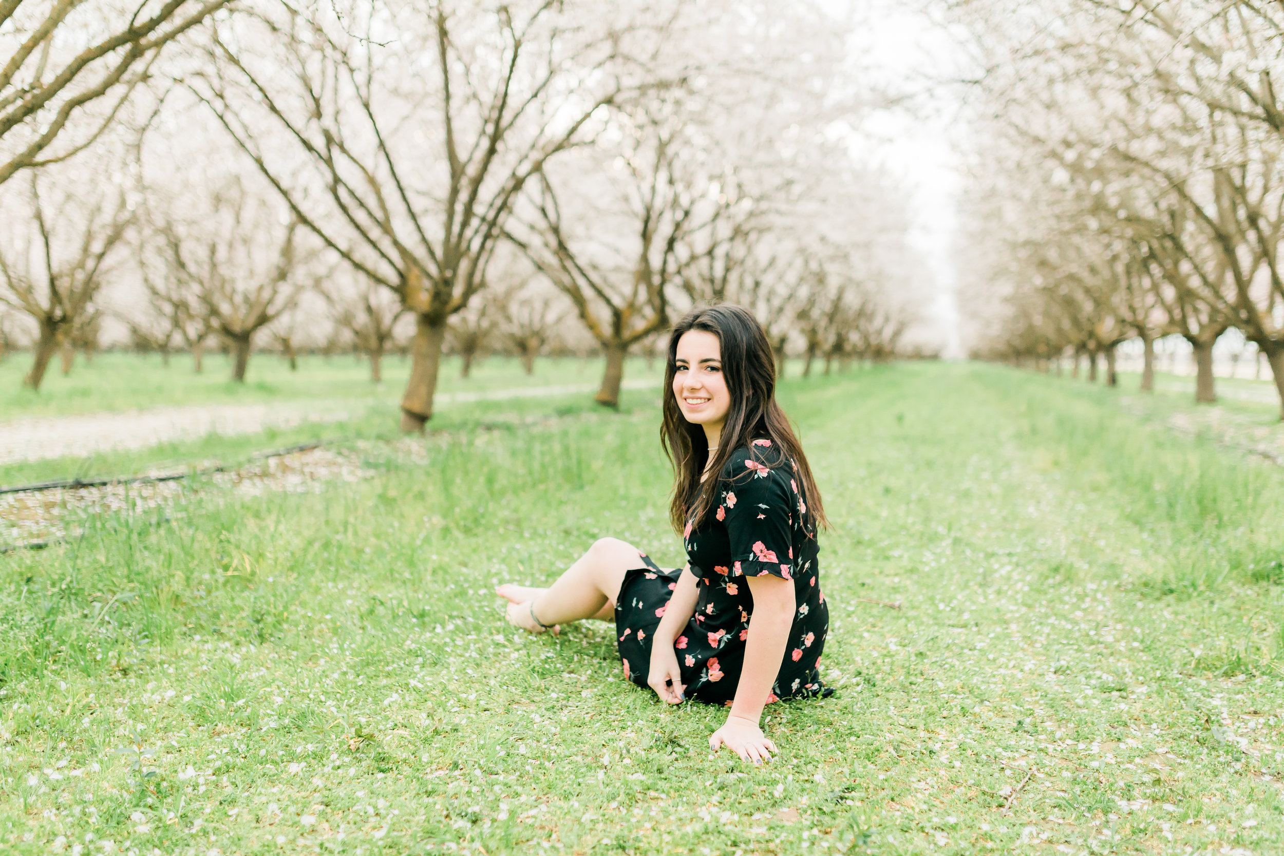senior girl sitting on grass in a blooming orchard
