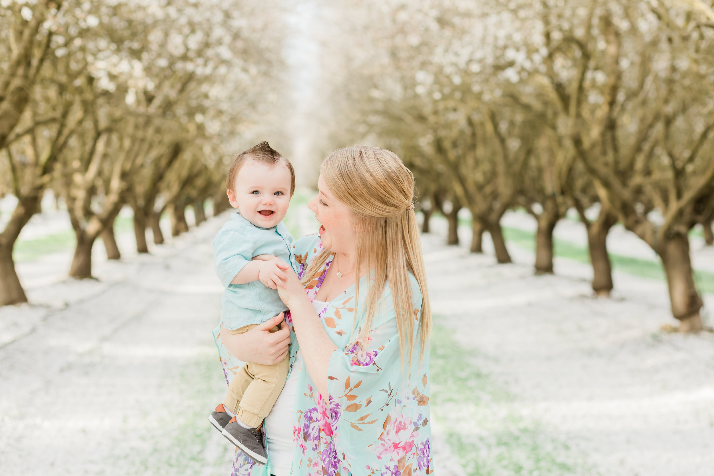 mother holding 9mo baby boy in blossoming orchard