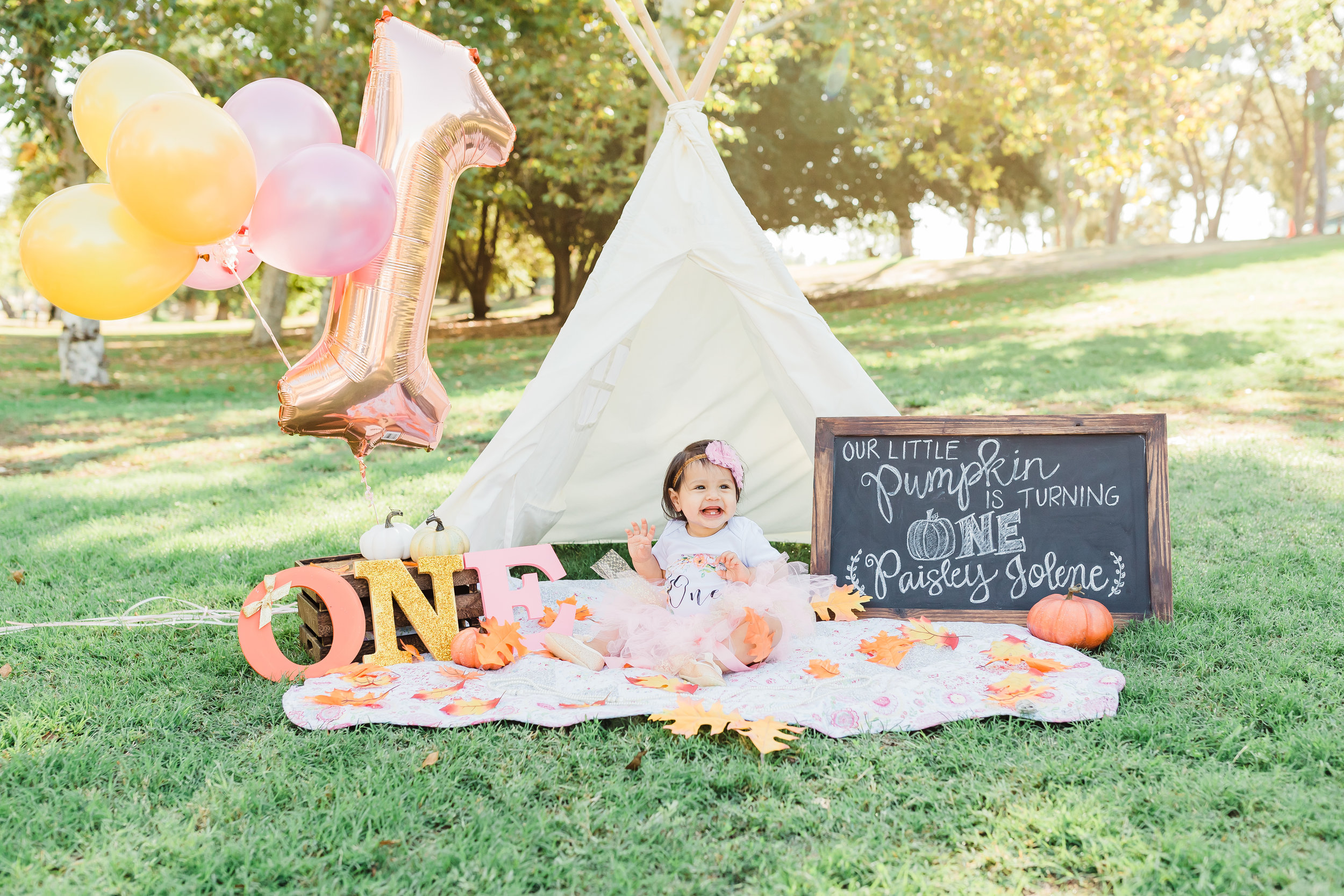 One year old girl sitting on the ground with tee pee tent and pumpkin decor to celebrate her one year birthday.