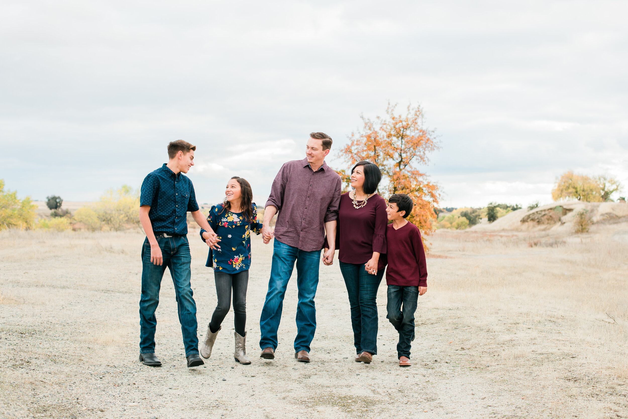 Fall family mini photos. Family standing, looking at each other, wearing fall colors with navy and burgundy.