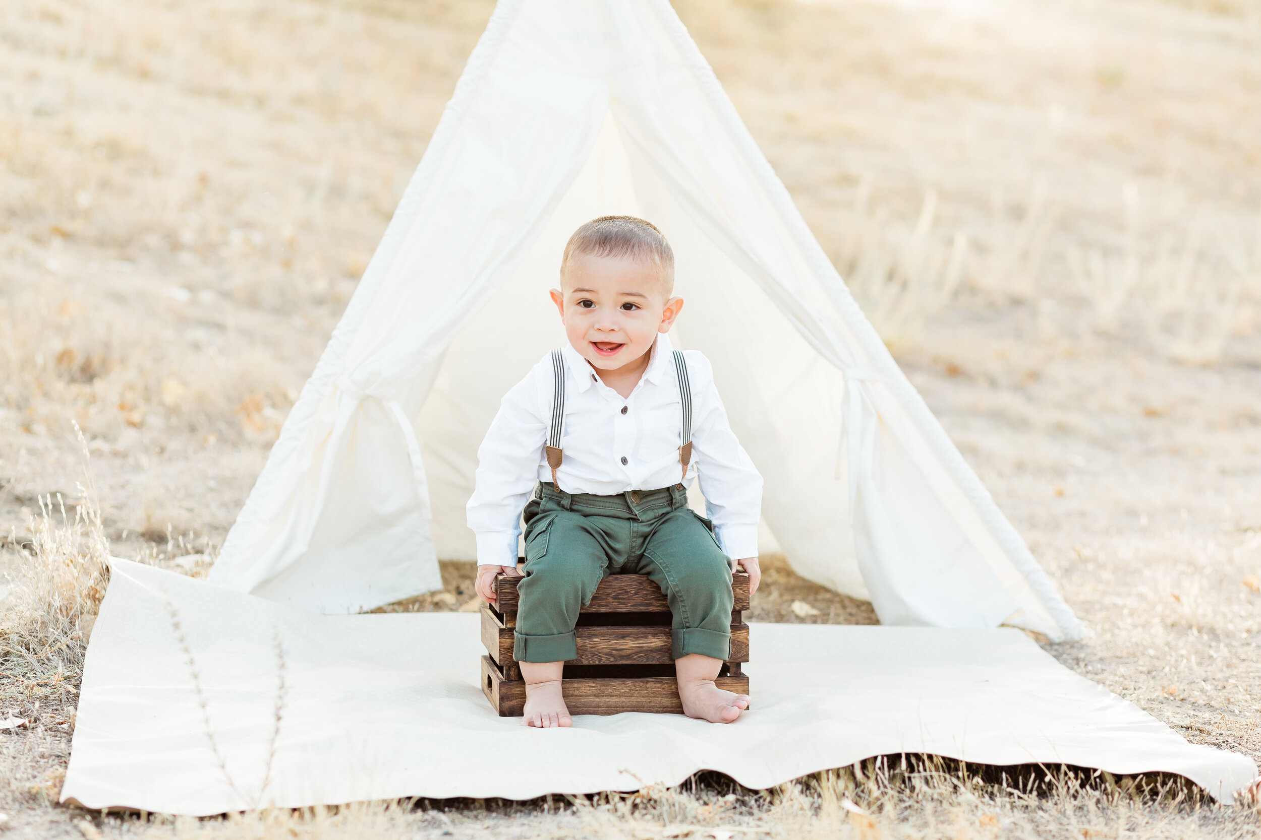 Cake Smash photo session, one year old boy wearing green pants and suspenders poses in front of a tee pee tent.