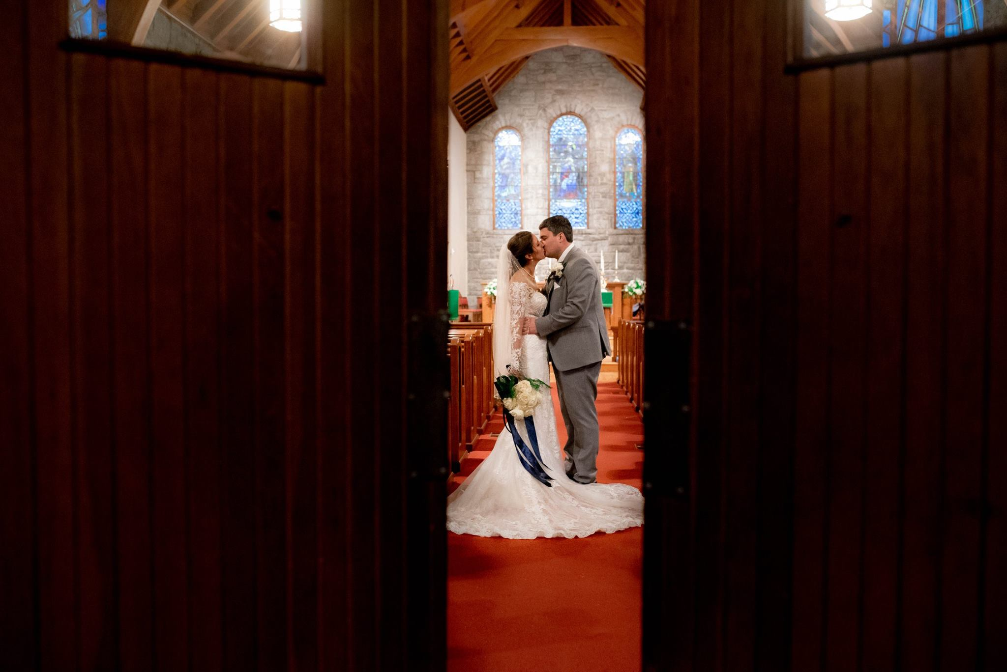 COUPLE KISSING AT St. Philip's Episcopal Church IN BREVARD, NORTH CAROLINA JUST AFTER THEIR BEAUTIFUL CEREMONY. NEXT THEY ARE OFF TO THEIR INCREDIBLE RECEPTION AT THE INN AT BREVARD.