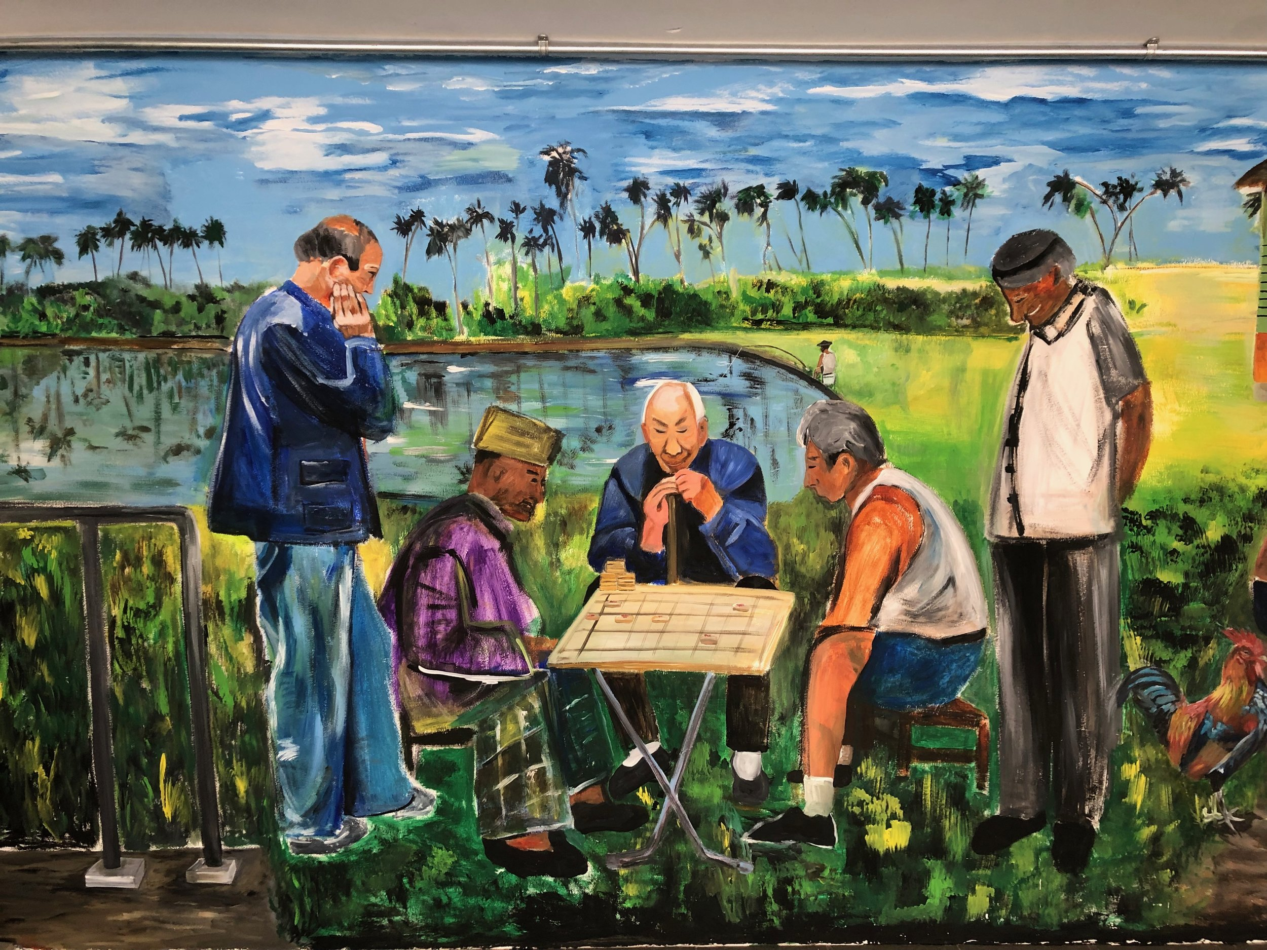 After the pond image, we see the men having a game of chess. This is my second wall painting of chess players (after the one at Chinatown) this time I added more people to depict how the different races lived together in harmony as Singapore is a multi-racial society.