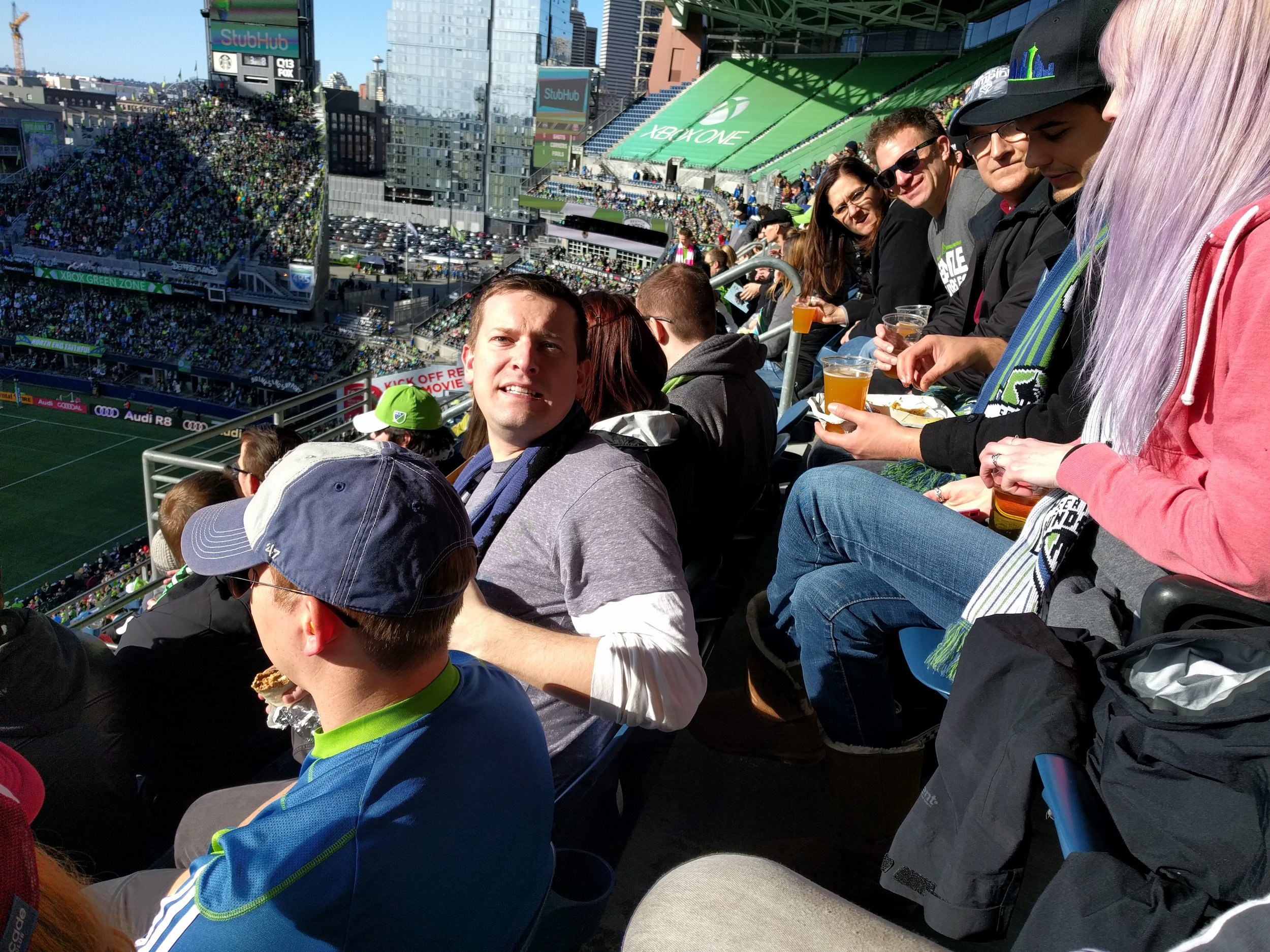 """Board Member Jack Reynolds, seen here striking his """"Growl-like-a-tiger"""" pose, surrounded by other amazing community members, donors, and volunteers cheering for the 2016 MLS Cup Champion Sounders at the 2017 Home Opener."""