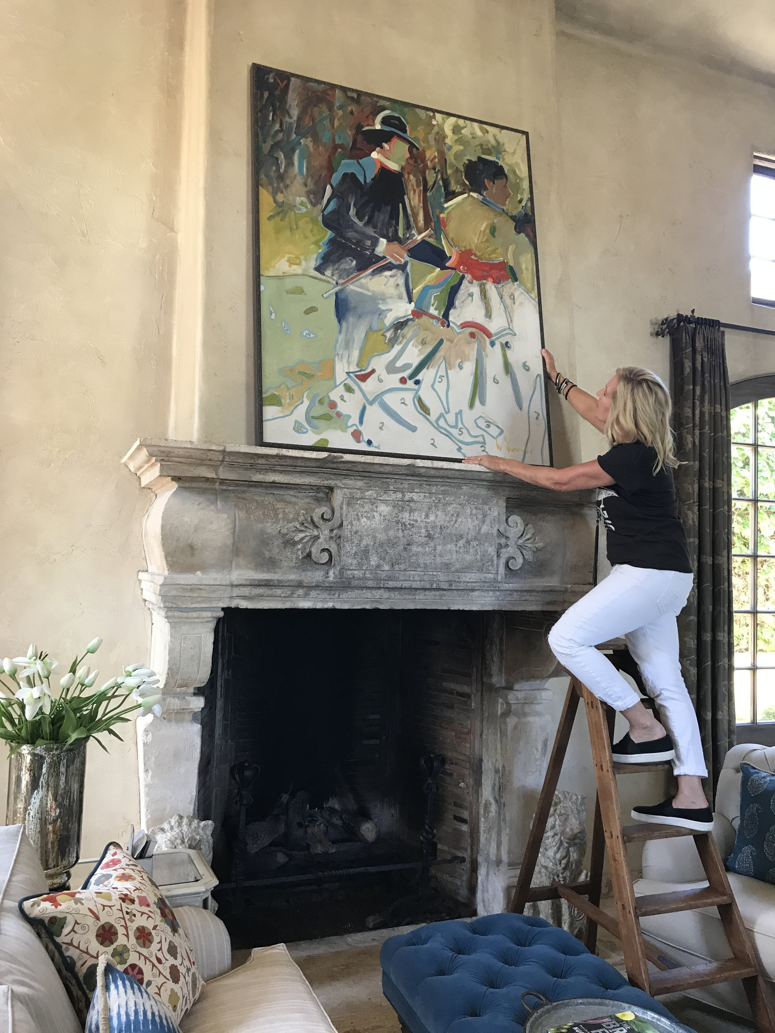 Naomi placing artwork in client's living space