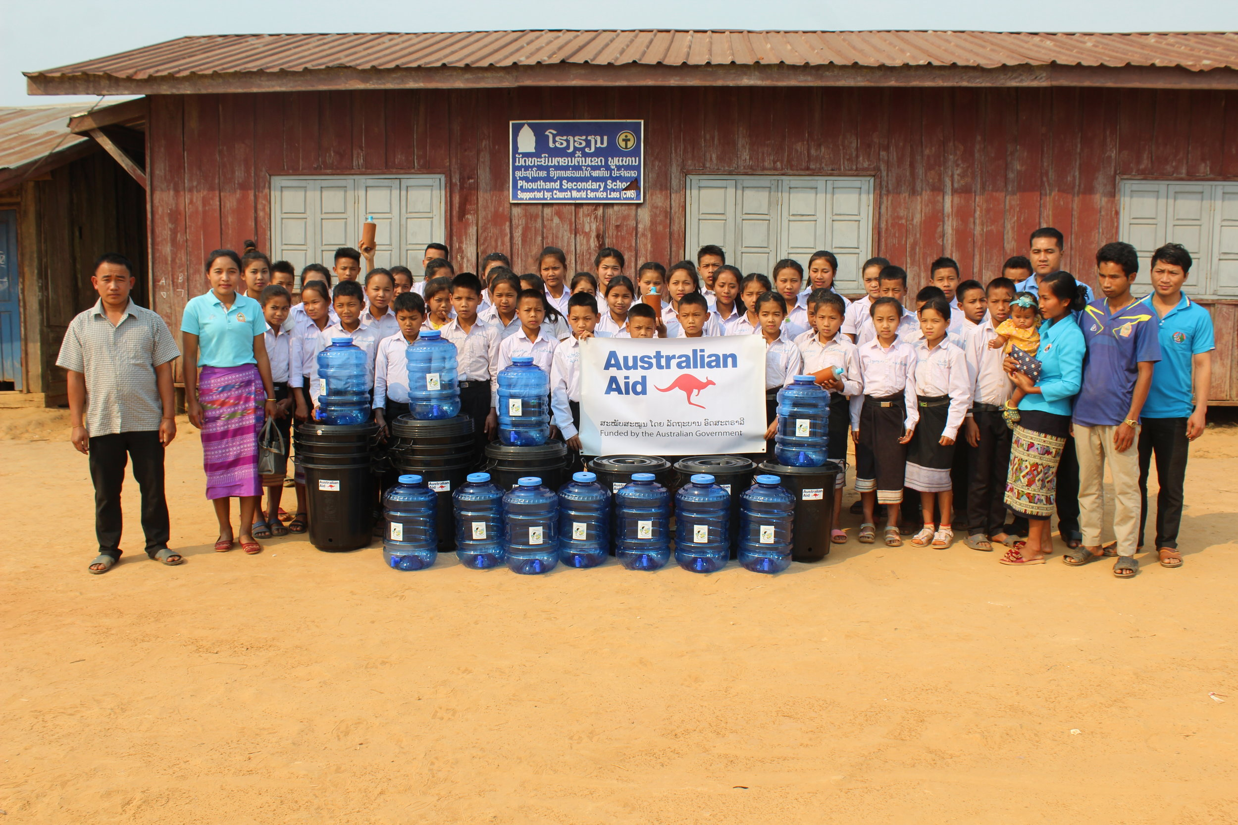 Students at Phoutaen Secondary School take a picture with Abundant Water filter sets that were installed with funding from the DFAT Direct Air Program.