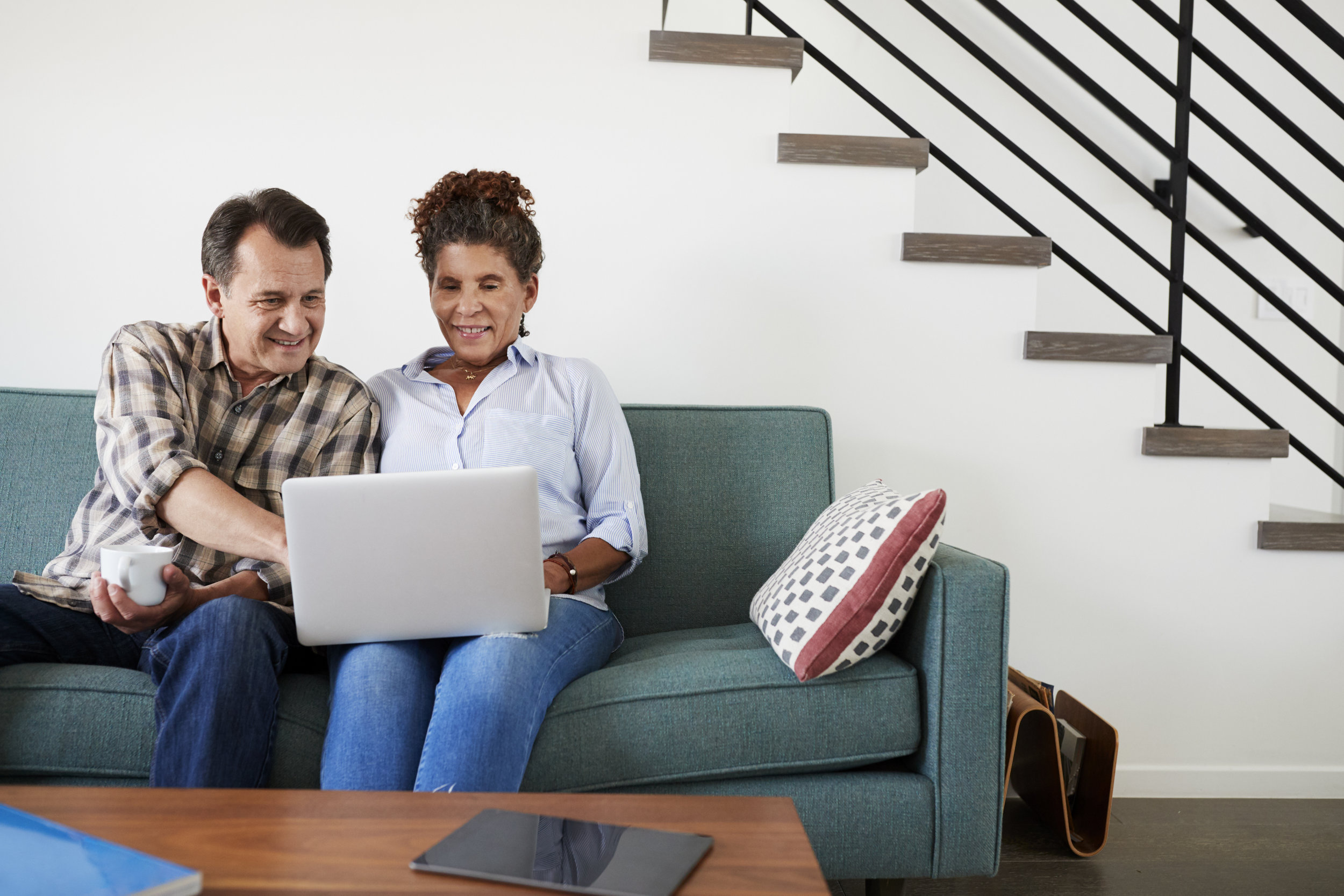 senior-couple-sitting-on-sofa-at-home-using-GSULYQB.jpg