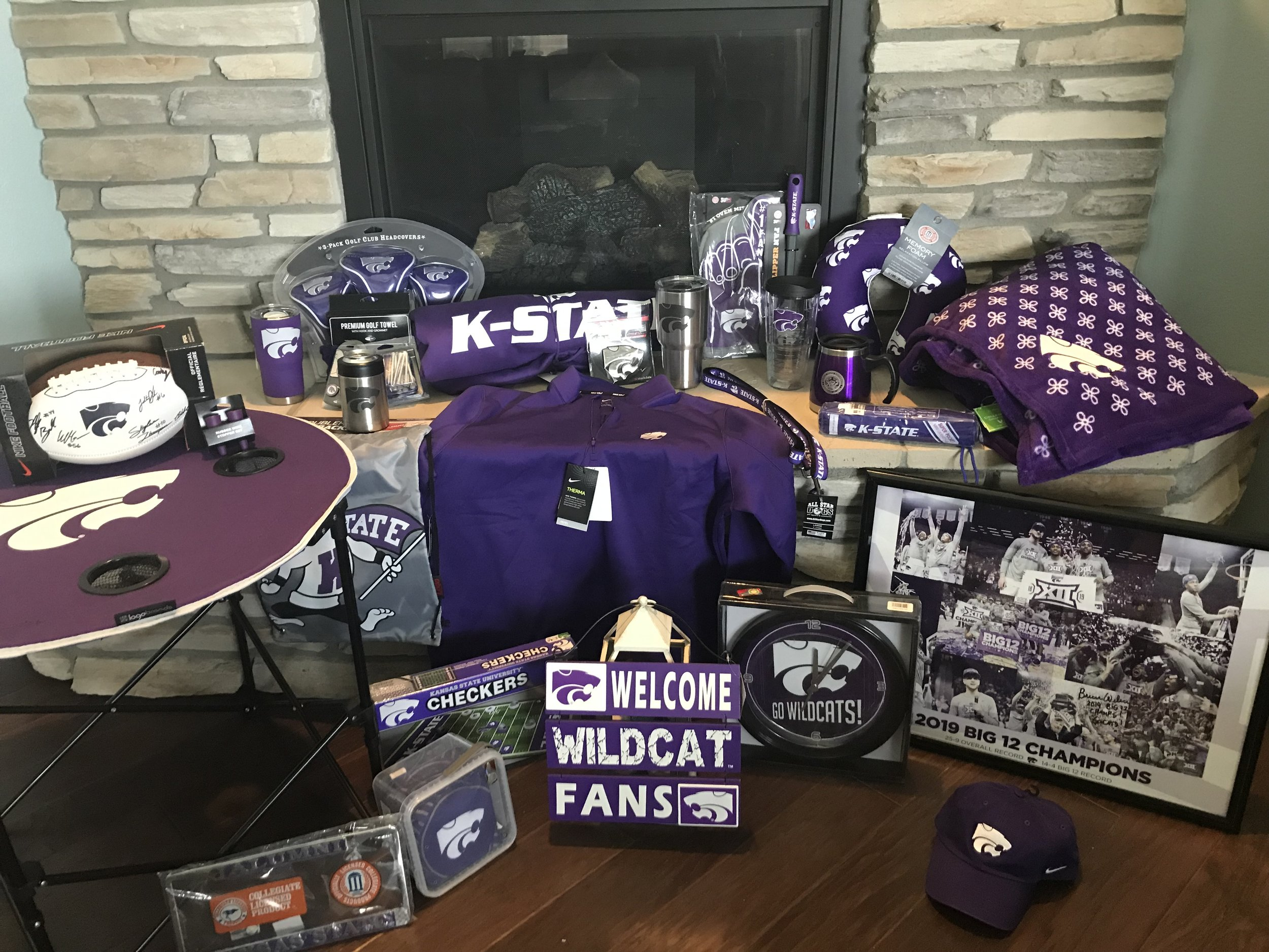 2019 Silent Auction Items   Clockwise from upper left: Powercat camp table, Signed football, Wine bottle stoppers, Powercat purple tumbler, Powercat aluminum can cooler, Classic Willie flag, 3-Pack Powercat golf wood head covers, Powercat golf towel, K-State throw blanket, Powercat Nike pullover, Powercat car emblem, Powercat silver tumbler, #1 Powercat oven mitt, K-State dog leash, Powercat clear tumbler, Spatula, K-State seal coffee mug, Memory foam neck pillow, K-State umbrella, Powercat blanket, Signed 2019 Big 12 Champions poster, Powercat cap, Powercat Go Wildcats clock ,Powercat Welcome's Wildcat Fans sign, K-State checkers game, Powercat beanbag toss game, Kansas State Alumni vanity license plate cover.