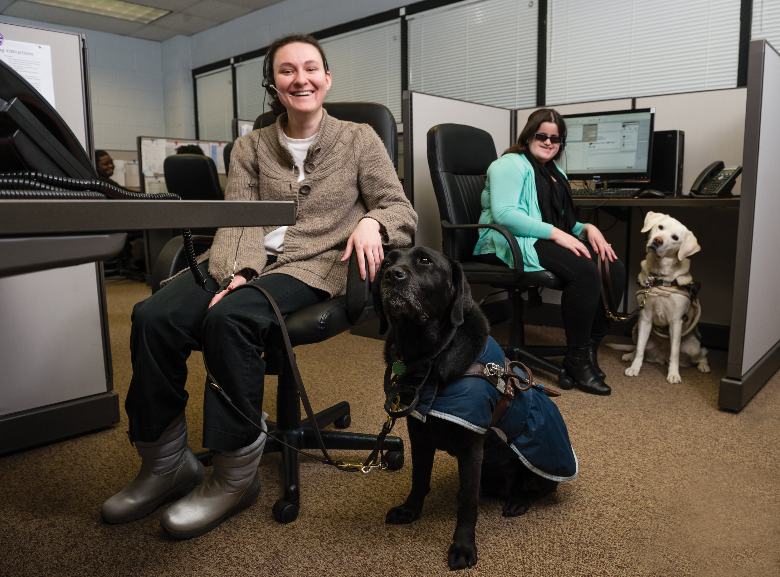 Lighthouse call center employees pose at their stations, each with their trusted guide dogs by their sides.