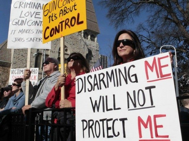 Protesters hold sign at the Guns Across America rally in Atlanta, GA, January 19, 2013. Source: REUTERS/Tami Chappell