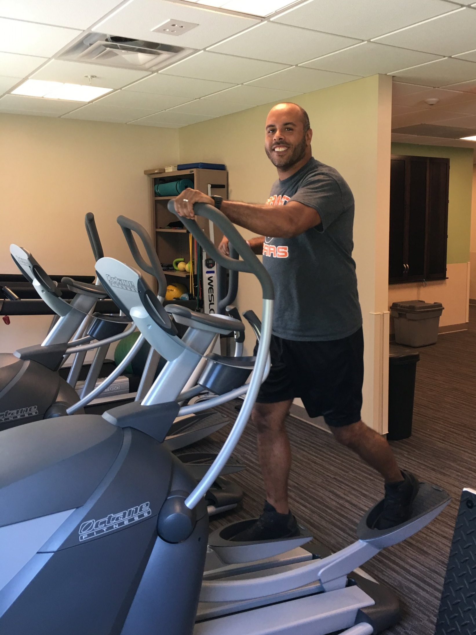 Health and Wellness Coordinator Jim Franklin demonstrates an elliptical at the new fitness center.