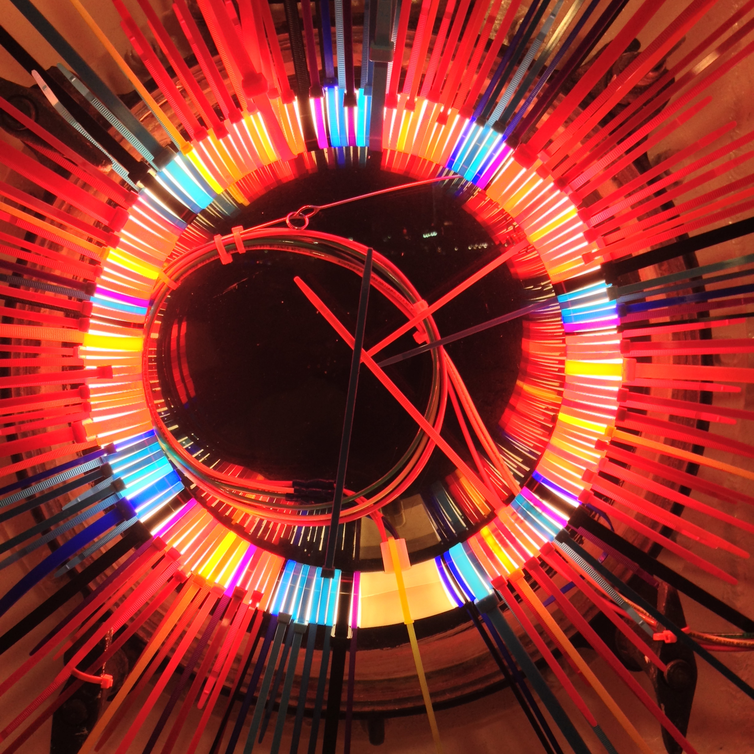 Red Mess   Fluorescent Lamp, color snap ties, loom heddles and fishing spinners and color wire 12 in lamp diameter 20 in overall