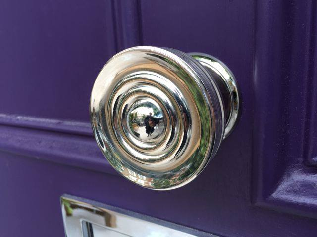A purple front door with gleaming chrome hardware. Purple chosen to work with the beautiful wisteria that covers the building walls.