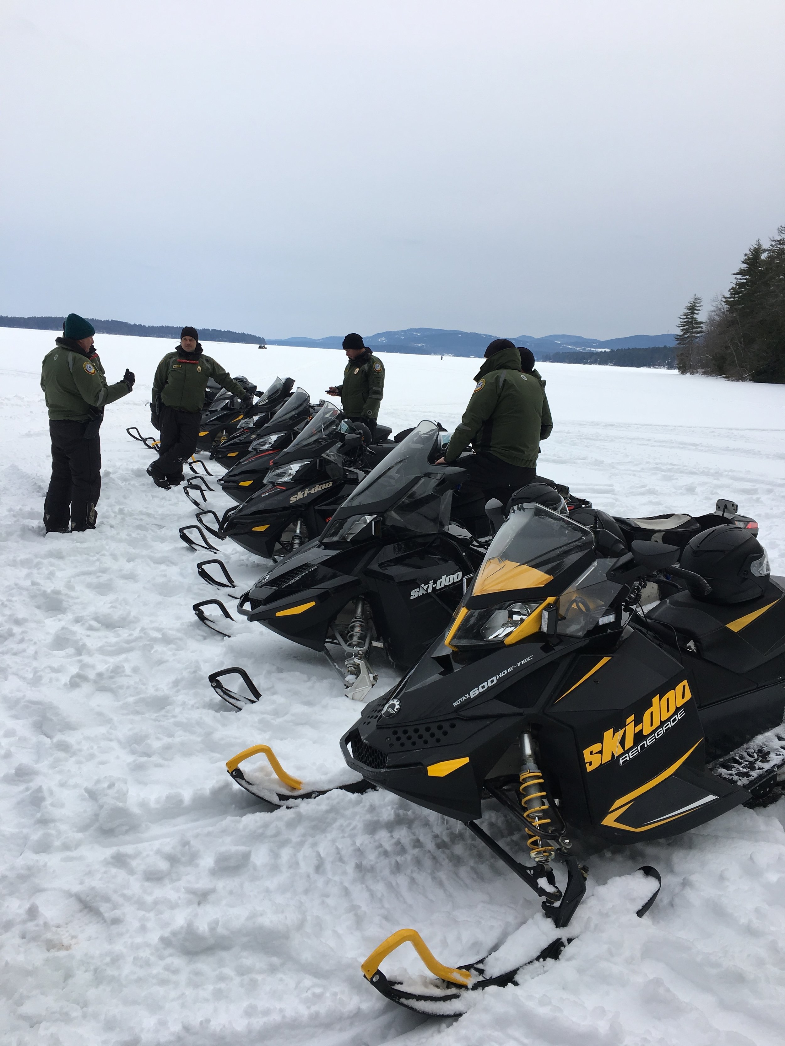 New Hampshire Fish and Game snowmobiles line up on the ice