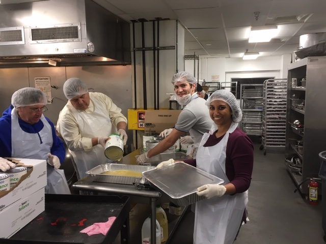 Four members of the Cleveland Club of Washington, D.C., transfer apple sauce from can to pan in the Club's effort to deliver balanced meals to Washington's hungry.