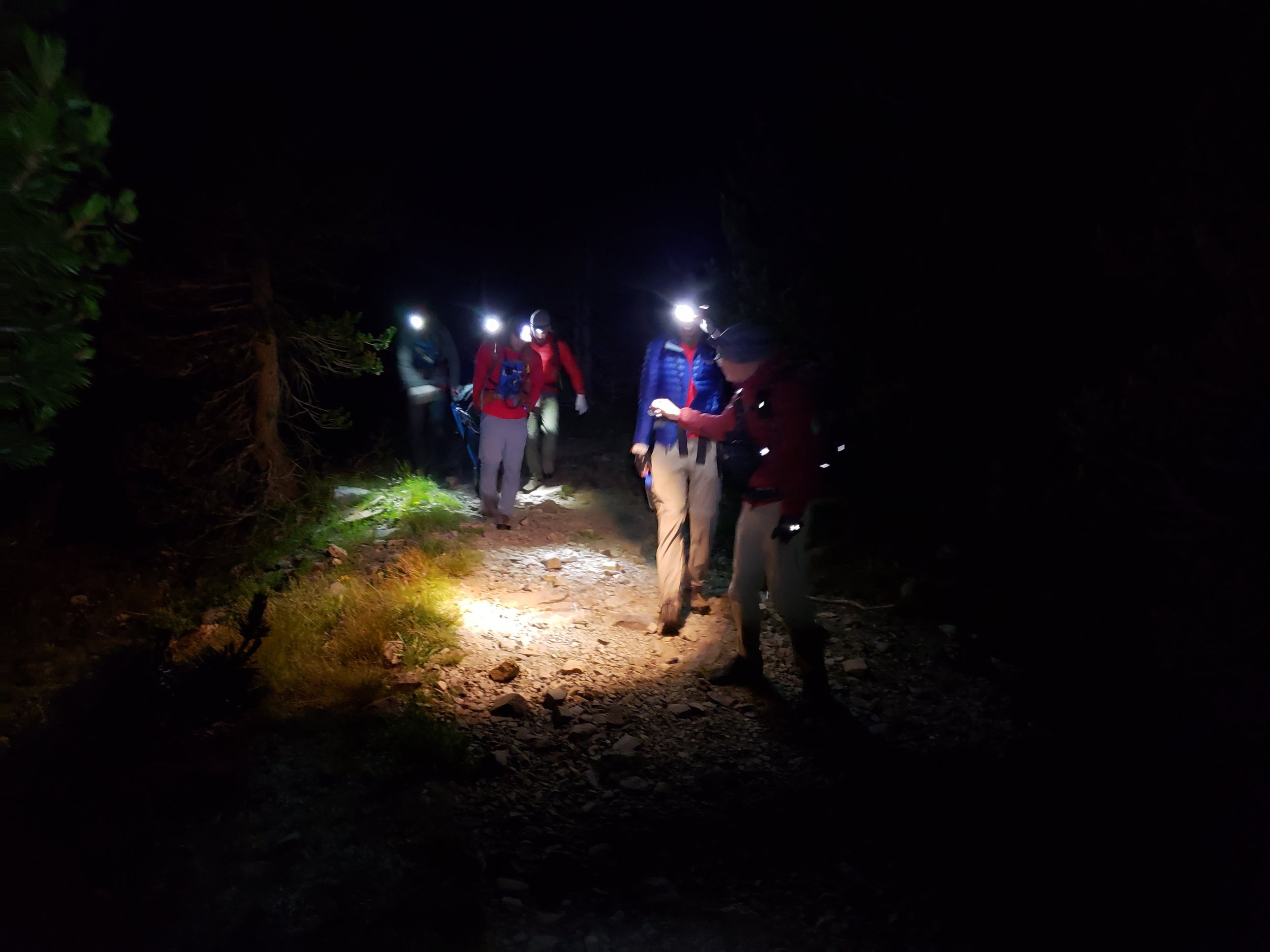 Rolling the litter down the dark and quiet trail back to the lake and the return boat ride.  Image by B. Beck