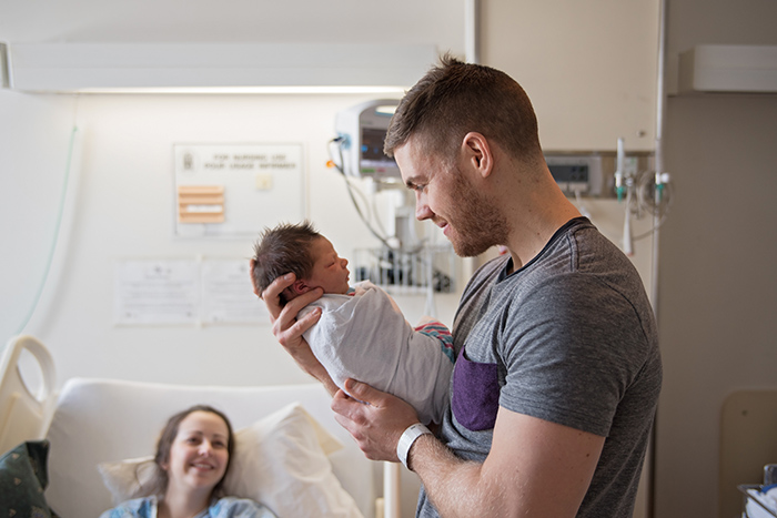 a father holds his newborn in hospital while the mother looks on lovingly in the background