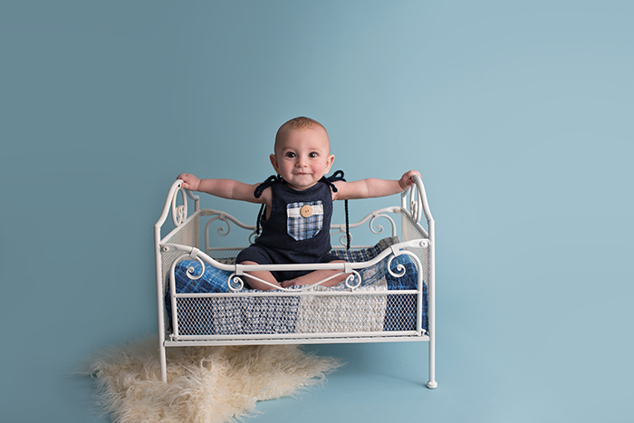 a baby sits in a cream iron bed with blue quilt wearing a navy upcyled romper in ottawa photography studio for milestone sitter