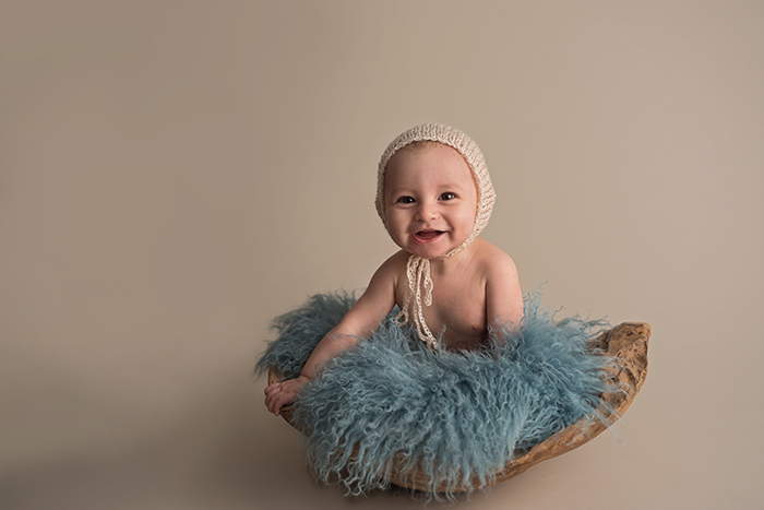 a baby sits in a wood bowl with blue fur stuffer wearing a cream bonnet smiling
