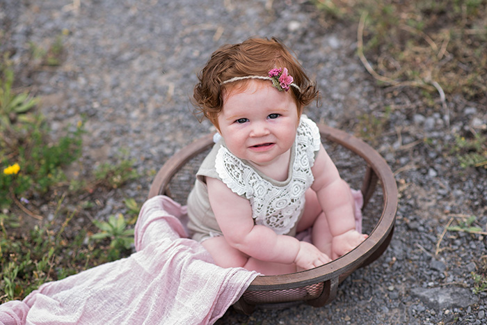 a red haired baby sits in wood bowl wearing green upcycled romper and tieback looking up at the camera