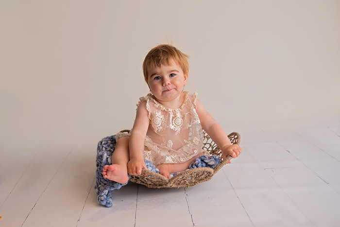 a one year old baby sits in a basket wearing a lace outfiti ottawa photography studio