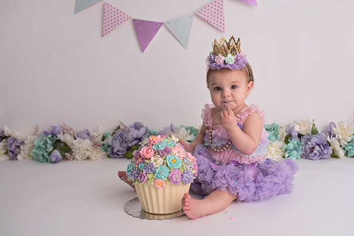 a baby sits in a tutu wearing a crown with floral background eating a flower cake for her milestone smash session in studio